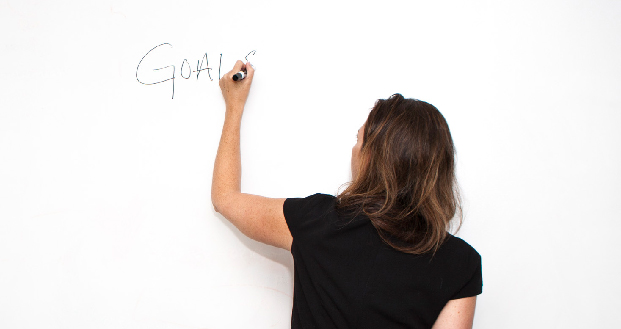 Woman writing 'goals' on whiteboard